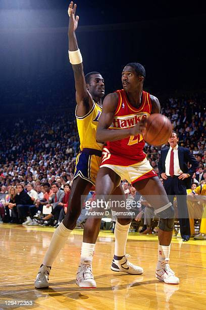Dominique Wilkins of the Atlanta Hawks drives against Michael Cooper of the Los Angeles Lakers circa 1987 at the Great Western Forum in Inglewood...
