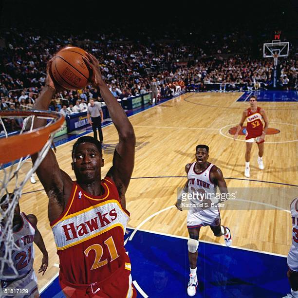 Dominique Wilkins of the Atlanta Hawks goes for a dunk against the New York Knicks during the NBA game circa 1991 at Madison Square Garden in New...