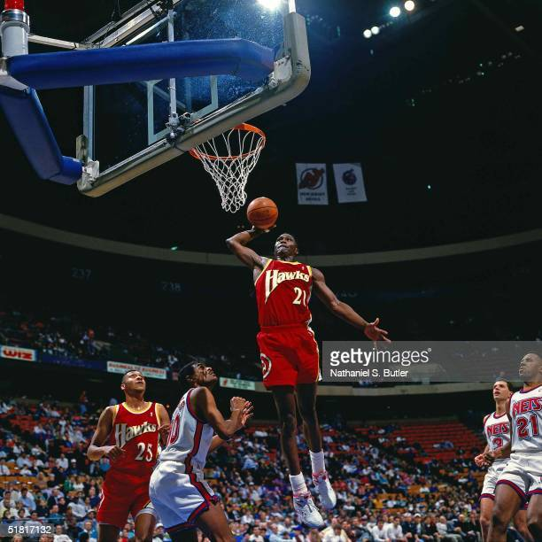 Dominique Wilkins of the Atlanta Hawks goes for a dunk against the New Jersey Nets during the NBA game circa 1993 in East Rutherford , New Jersey....