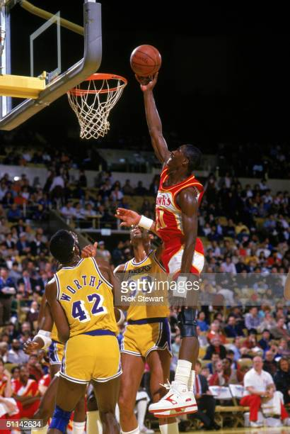 Dominique Wilkins of the Atlanta Hawks goes up for a layup against James Worthy and Kareem AbdulJabbar of the Los Angeles Lakers during a 1986 NBA...