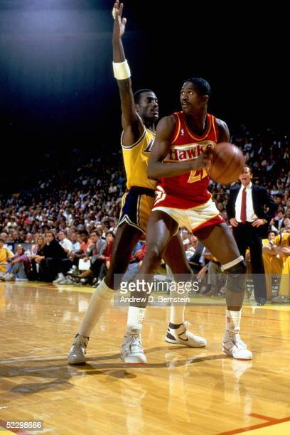 Dominique Wilkins of the Atlanta Hawks looks for a teammate to pass to against the Los Angeles Lakers circa 1987 during an NBA game at the Forum in...