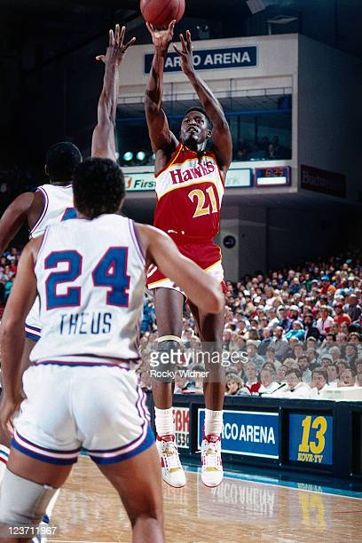 Dominique Wilkins of the Atlanta Hawks shoots against Reggie Theus of the Sacramento Kings on December 13 1987 at Arco Arena in Sacramento California...