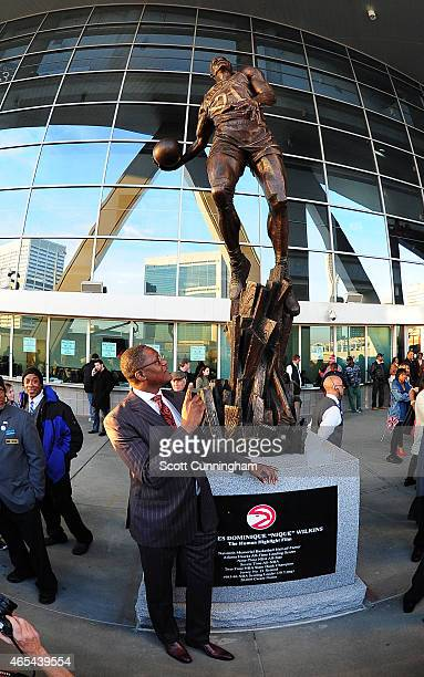 Dominique Wilkins poses by his statue before the game between the Atlanta Hawks and the Cleveland Cavaliers on March 6 2015 at Philips Arena in...