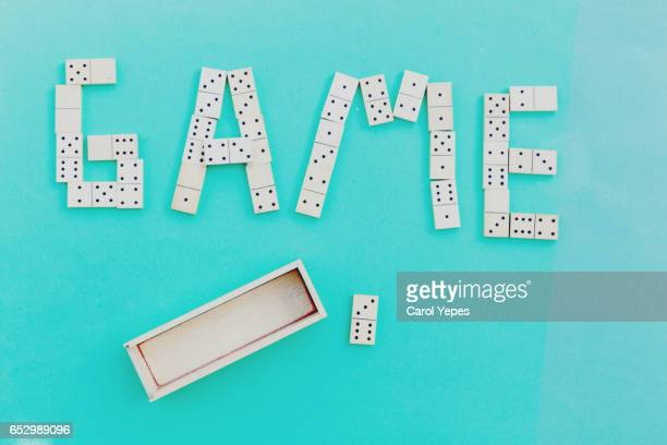 domino pieces forming the word GAME.Top view