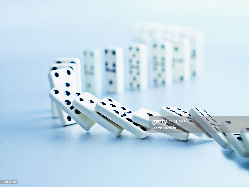 Dominoes falling in a row : Stock Photo