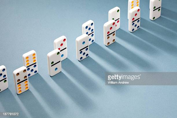 Dominoes lined up, casting shadow