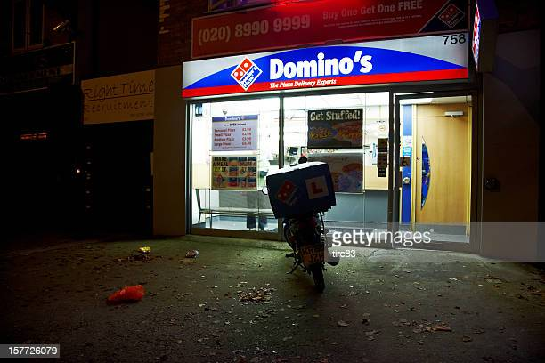 Dominos pizza delivery vehicle and restaurant at night