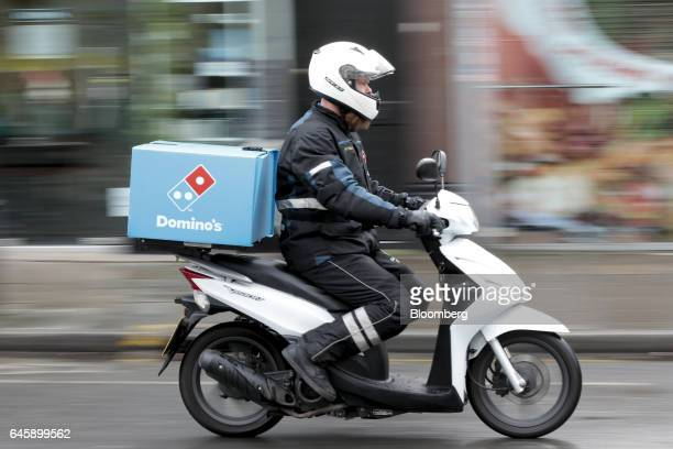 A Domino's Pizza food delivery courier drives a moped away from a Domino's Pizza Group Plc store in Hanwell London UK on Monday Feb 27 2017 Domino's...
