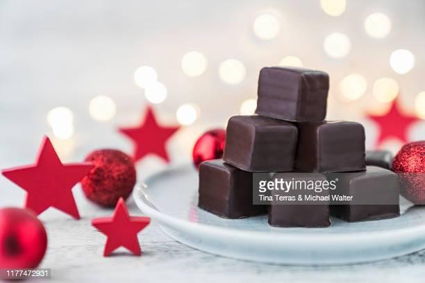 dominosteine (chocolate pralines) on a plate with christmas decoration. - tina terras michael walter stock-fotos und bilder