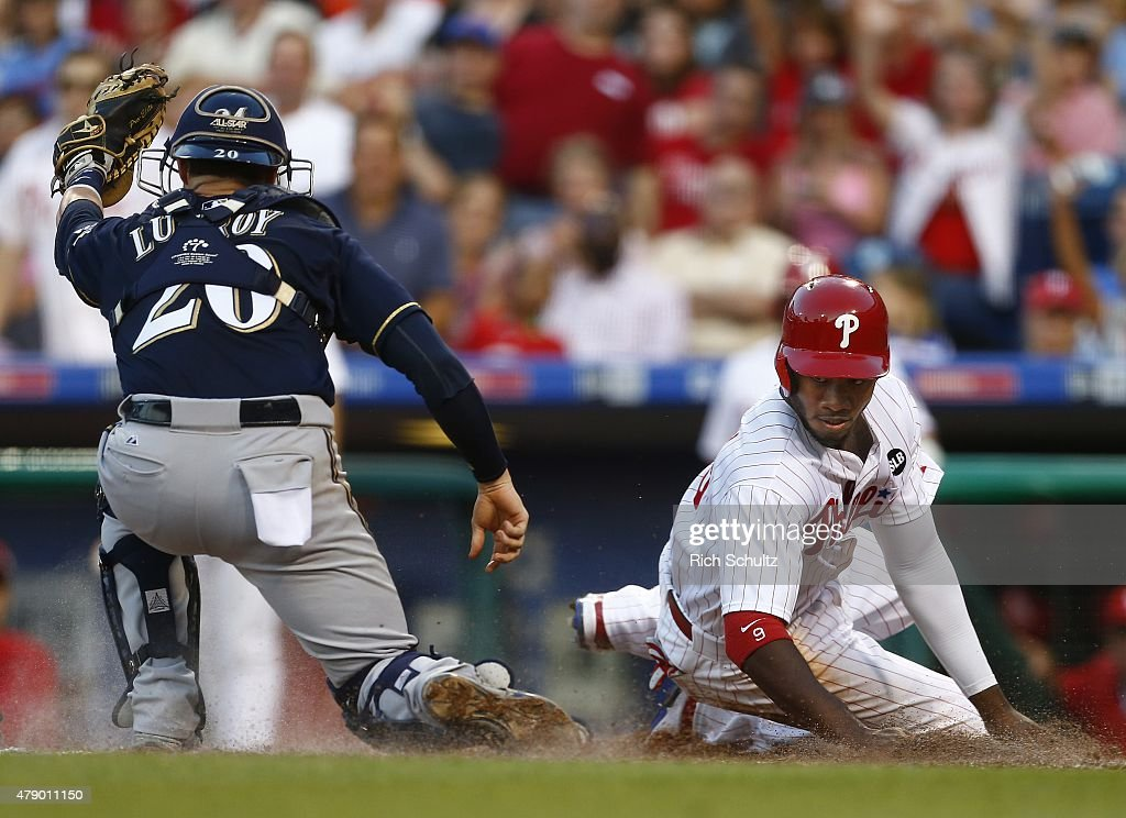 Domonic Brown #9 of the Philadelphia Phillies is called out at home plate after catcher Jonathan Lucroy #20 of the Milwaukee Brewers makes the tag on a double by the Phillies Cody Asche #25 during the third inning of a MLB game at Citizens Bank Park on June 29, 2015 in Philadelphia, Pennsylvania.