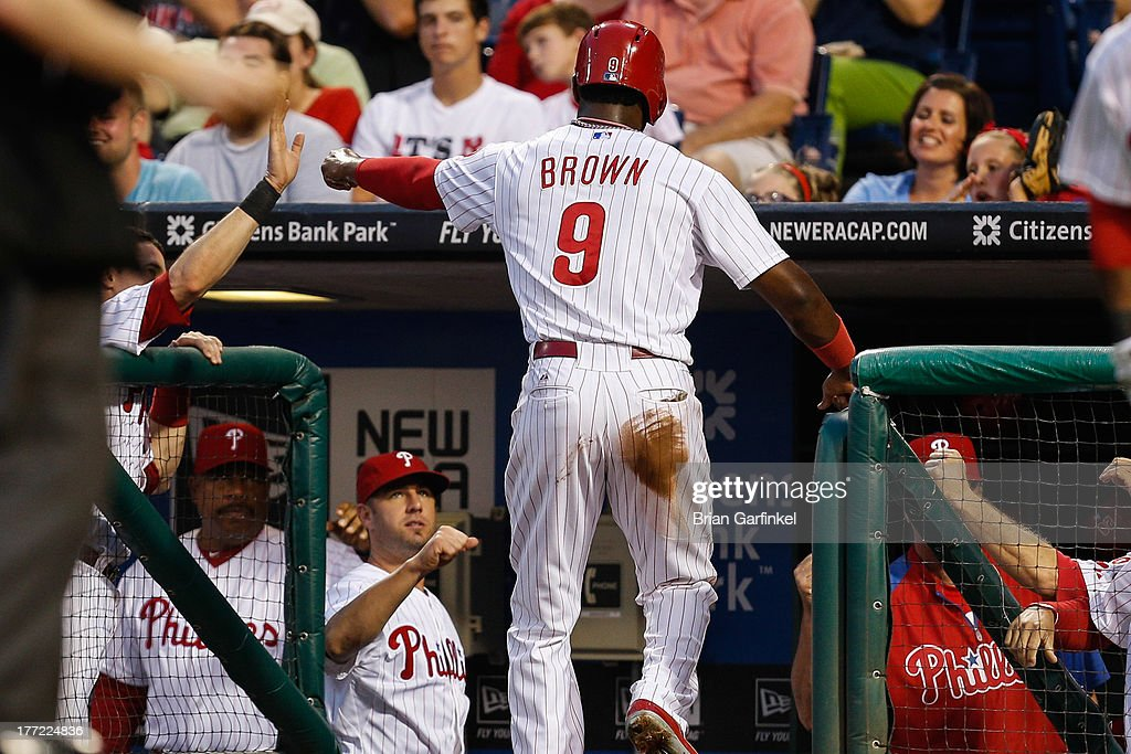 Domonic Brown #9 of the Philadelphia Phillies is congratulated in the dugout after scoring a run in the second inning of the game against the Colorado Rockies at Citizens Bank Park on August 22, 2013 in Philadelphia, Pennsylvania.