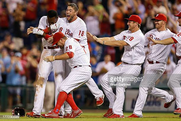 Domonic Brown of the Philadelphia Phillies is swarmed by teammates after hitting an RBI single to send the game winning run home in the bottom of the...