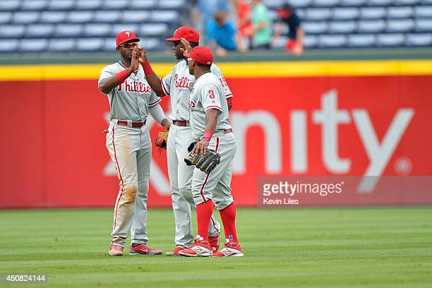 Domonic Brown of the Philadelphia Phillies John Mayberry Jr #6 and Marlon Byrd celebrate defeating the Atlanta Braves 105 at Turner Field on June 18...