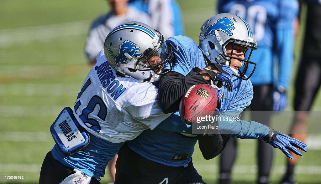 Domonique Johnson #46 and Matt Willis #12 of the Detroit Lions battle for the ball during training camp on July 30, 2013 in Allen Park, Michigan.