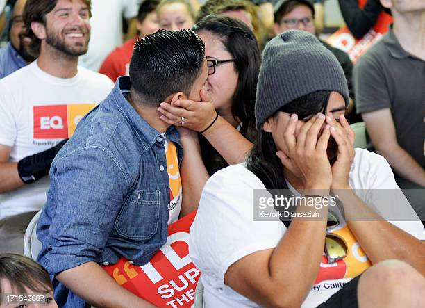 Domstic partners Alicia Guajardo and Isabella Restrepo kiss as Martha Acevedo reacts to the Supreme Court ruling at a watch party at Equality...