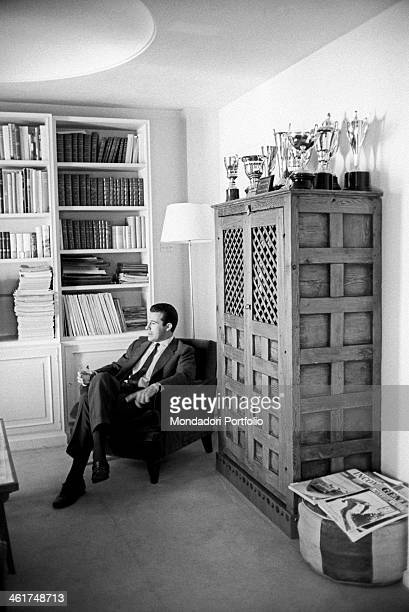 Don Alfonso grandson of king Alfonso XIII sits in an armchair in his house near a stocked library on the top of a furniture beside are on display the...