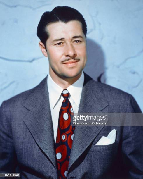 Don Ameche US actor wearing a grey suit jacket white shirt and red white and blue tie in a studio portrait against a light blue background circa 1940