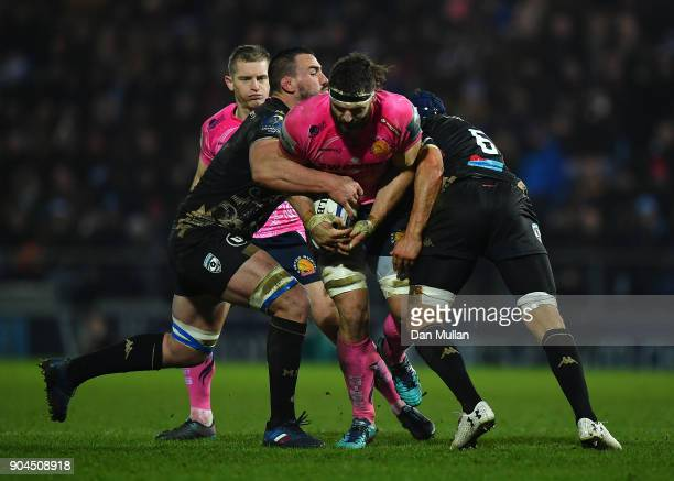 Don Armand of Exeter Chiefs is tackled by Louis Picamoles and Julien Bardy of Montpellier during the European Rugby Champions Cup match between...