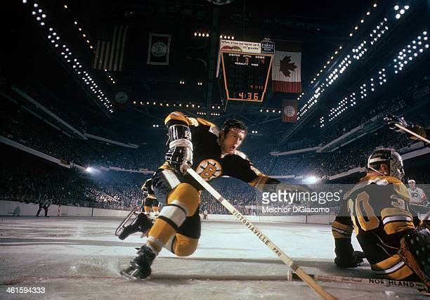 Don Awrey of the Boston Bruins falls towards the net behind goalie Gerry Cheevers during an NHL game against the Philadelphia Flyers circa 1969 at...