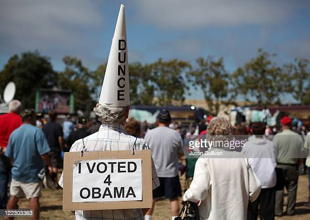 Don Bahl wears a dunce hat and a sign stating that he voted for U.S. President Barack Obama during the Tea Party Express tour kick-off on August 27,...