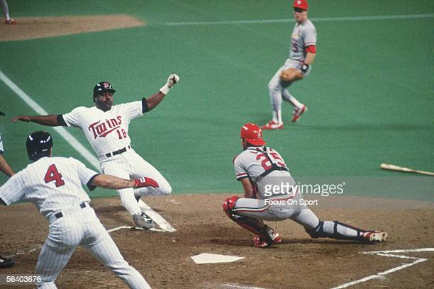 Don Baylor of the Minnesota Twins slides into home base as Steve Lake of the St Louis Cardinals waits to make the tag during the World Series at the...