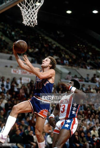 Don Buse of the Phoenix Suns lays the ball up in front of John Williamson of the New Jersey Nets during an NBA basketball game circa 1979 at Nassau...