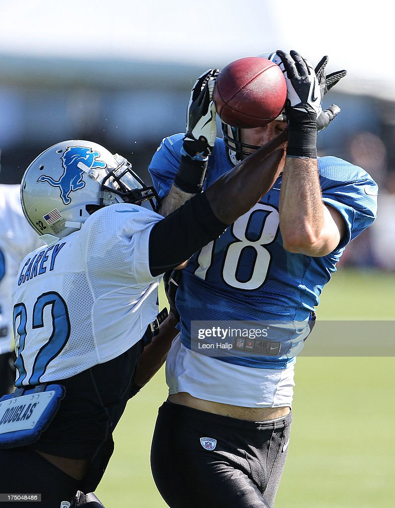 Don Carey #32 and Kris Durham #18 of the Detroit Lions battle for the ball during training camp on July 30, 2013 in Allen Park, Michigan.