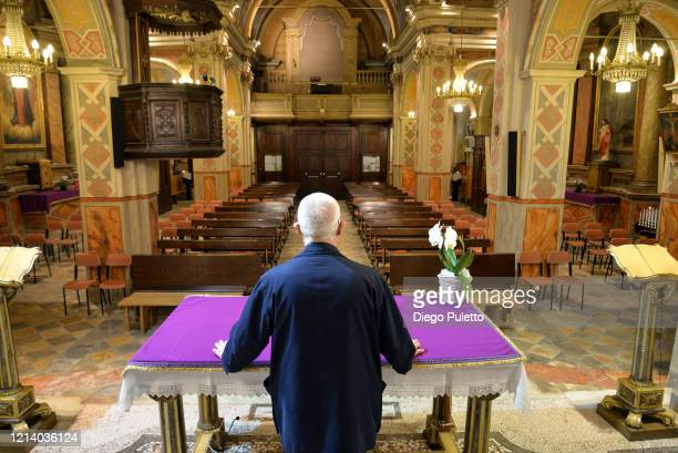 Don Carlo Chiomento parish priest of the church of Candiolo wears a mask in a deserted church on March 22 2020 in Turin Italy The Italian government...