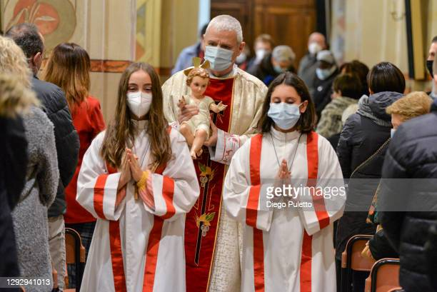 Don Carlo Chiomento Parish priest of the Community of Candiolo carries baby Jesus during the celebration of the Holy Mass on Christmas on December...