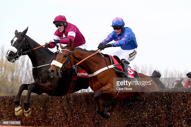 Don Cossack ridden by Tony McCoy and Cue Card ridden by Daryl Jacobs compete in the Betfred Melling Steeple Chase at Aintree Racecourse on April 10...