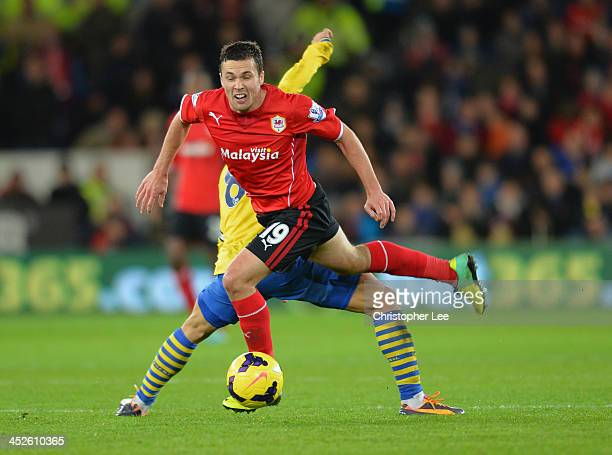 Don Cowie of Cardiff is tackled by Mikel Arteta of Arsenal during the Barclays Premier League match between Cardiff City and Arsenal at Cardiff City...