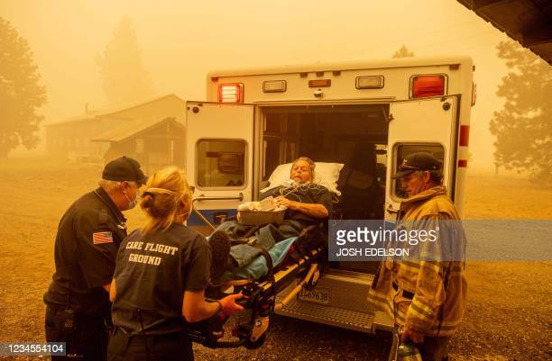 Don Crail , whose home burned down, is rushed into an ambulance for a medical issue in Greenville, California on August 7, 2021. - The Dixie Fire has...