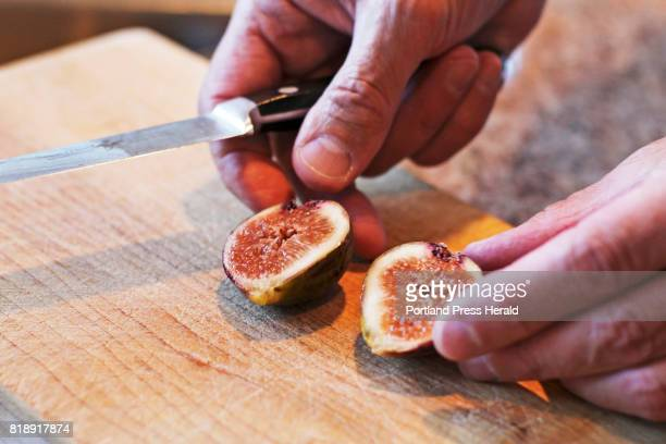 Don Endrizzi, the son of Italian immigrants, cuts open a fresh fig from his tree at his home in Scarborough. Don is using his grandfathers cutting...
