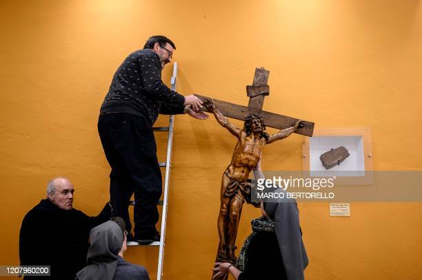 Don Giovanni Banchio holds a wooden crucifix at the end of the streaming of Sunday mass in the Chapel of the San Giovanni Bosco Oratory on March 22...