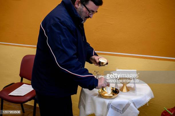 Don Giovanni Banchio prepares hosts beforecelebrating the streaming of the Sunday mass in the Chapel of the San Giovanni Bosco Oratory on March 22...