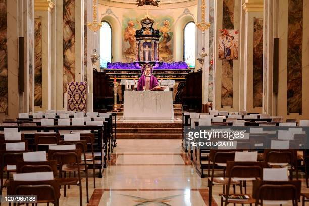 Don Giuseppe Corbari parson of the Church of Robbiano celebrates mass in front of empty church pews adorned with selfies sent by his congregation in...