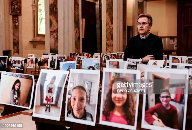 Don Giuseppe Corbari parson of the Church of Robbiano poses amidst selfie photographs in sent by his congregation and glued to empty church pews in...