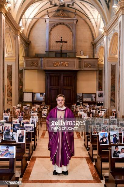 Don Giuseppe Corbari parson of the Church of Robbiano poses between selfie photographs sent in by his congregation members and glued to empty pews...