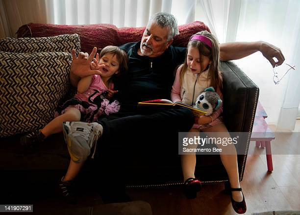 Don Hatfield center interacts with his grandchildren Ariel left and Eva as they read 'One Fish Two Fish Red Fish Blue Fish' in a Napa California home...