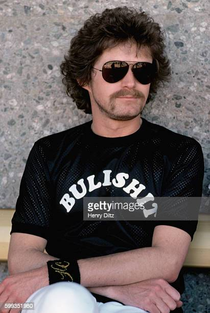 Don Henley drummer of the Eagles sits on a bench during a charity baseball game He wears a shirt that says 'Bullshit' The Eagles were the most...