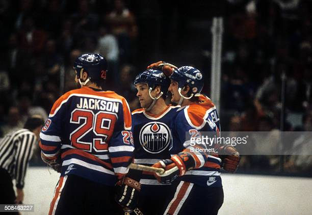 Don Jackson Dave Hunter and Kevin McClelland of the Edmonton Oilers celebrate on the ice after scoring a goal against the New York Islanders in Game...