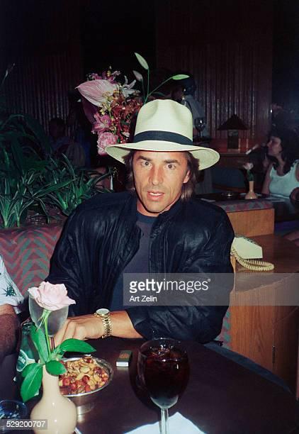 Don Johnson wearing a white hat seated at a bar circa 1980 New York