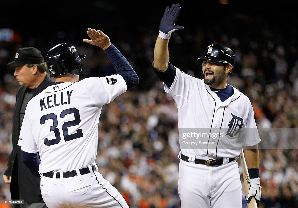 Don Kelly #32 and Alex Avila #13 of the Detroit Tigers celebrate after Kelly scored on a double by Jhonny Peralta #27 in the sixth inning of Game Three of the American League Division Series against the New York Yankees at Comerica Park on October 3, 2011 in Detroit, Michigan.