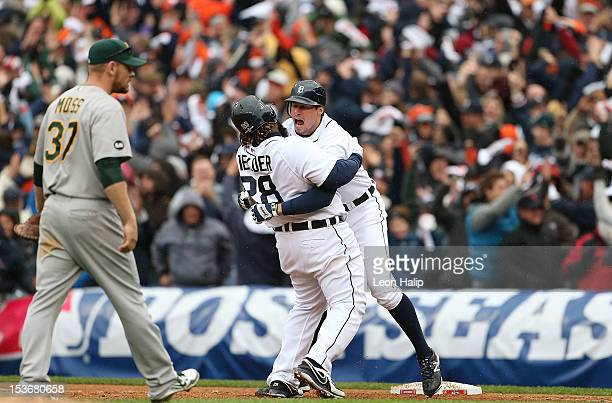 Don Kelly of the Detroit Tigers celebrates with teammate Prince Fielder after hitting a game winning sacrifice fly during Game Two of the American...