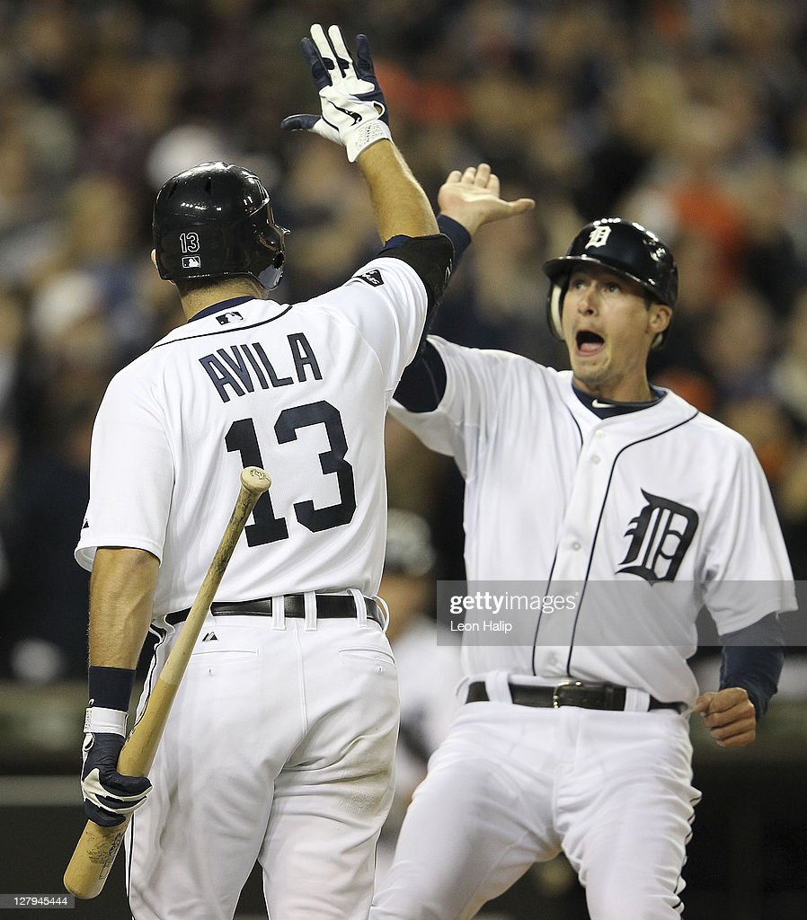 Don Kelly #32 of the Detroit Tigers scores on Jhonny Peralta #27 double to deep left field in the sixth inning and is congratulated by Alex Avila #13 during the game against the New York Yankees at Comerica Park on October 3, 2011 in Detroit, Michigan.