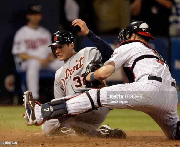 Don Kelly of the Detroit Tigers slides safely into home plate to score as Joe Mauer of the Minnesota Twins applies the tag during the 10th inning of...