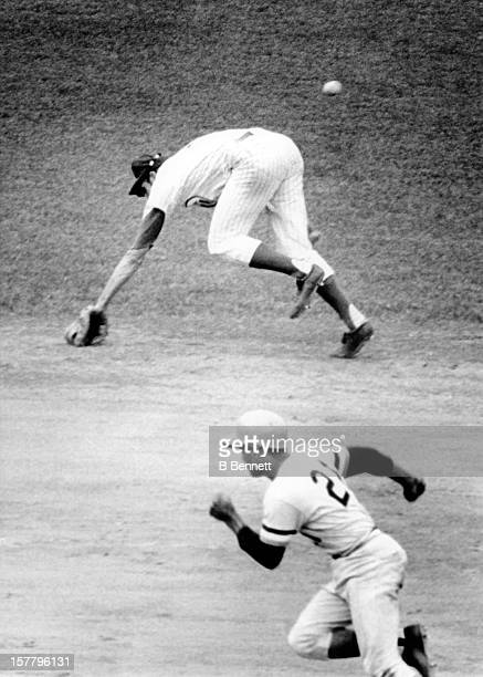 Don Kessinger of the Chicago Cubs misses the ball as Roberto Clemente of the Pittsburgh Pirates runs to third during their game on July 4 1971 at...