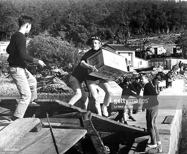 Don Knight lifts a crate as Aldo Ray looks on in a scene from the film 'Kill A Dragon' 1967