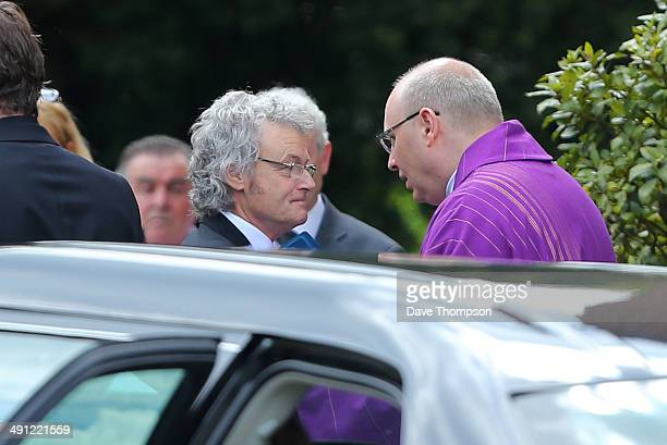 Don Maguire, left, is greeted by Monsignor Paul Fisher as he arrives at the Catholic Church of The Immaculate Heart of Mary for the funeral of Ann...