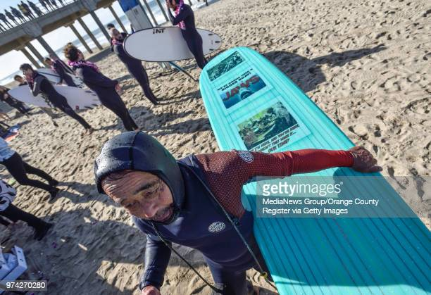 Don Nakamura heads out to sea with more than 100 surfers during a paddle out to honor Pierre Agnes CEO of Quiksilver in Huntington Beach on Friday...